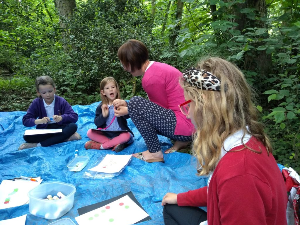 Children sitting on a blue tarpaulin making pictures of caterpillars